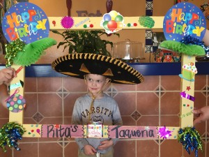 "A 4-year-old white boy wearing a black and gold Mexican sombrero standing awkwardly behind a large brightly decorated frame with ""happy birthday"" written on it in several places. His expression is partially smiling and partially perplexed."