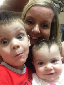 White woman center with a toddler boy and infant girl on either side. Close up headshot selfie of the three making silly faces.