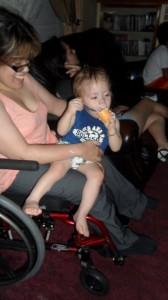 Mother sitting in wheelchair holding her young son