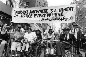 Image shows disability advocates marching before the ADA was passed