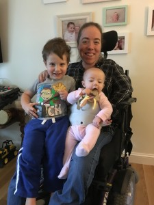 Photo of woman in wheelchair holding baby and toddler on her lap. Strap is around her and baby.