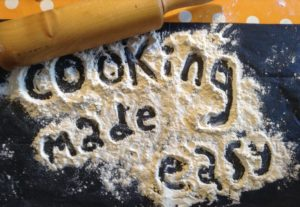 Rolling pin with flour. Cooking made easy written with flour on counter