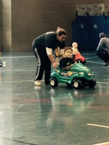 This is a photo of Tracie pushing her three-year-old son Desmond, and a green and yellow car inside a gymnasium where a toddler play date is taking place. Tracy has a determined look on her face as she pushes her son across the busy gymnasium floor. Warmly,