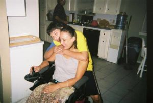 Photo of boy hugging woman in wheelchair. Both are smiling.