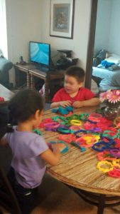 Photo of little boy and girl playing at table with toys spread out