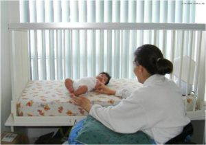 Photo of mother in wheelchair and baby in accessible crib.