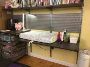 Photo shows baby changing table attached to book shelf and storage space