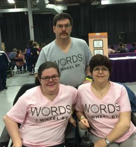 Photo of two women in wheelchairs and a man standing behind them. All three are wearing shirts that say Words I Wheel By