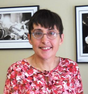 White woman wearing floral shirt and glasses, smiling at the camera