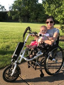 Mom sits in wheelchair with an attachment connected to the front with a motor. Baby is secured on mom's lap with a wide strap. Baby and mom are smiling outside.