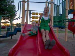 Woman and young boy going down slide at playground