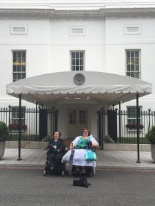 Two women sitting in their wheelchairs outside of the White House.