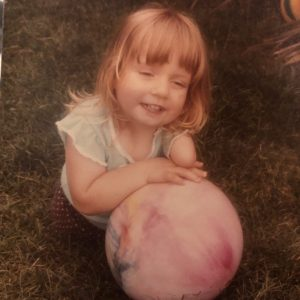Little blonde white girl with no legs and one arm playing with a big pink ball