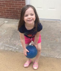 Young nondisabled brunette girl playing with blue ball