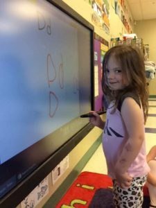 "Little white girl, age four, smiling holding a marker in front of a smart screen where she has written the letter ""D"" several times"