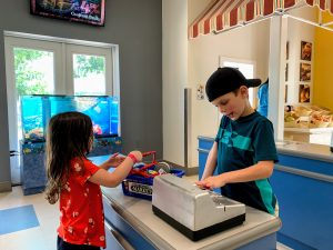 Two young kids playing in pretend store with fake groceries and toy cash register