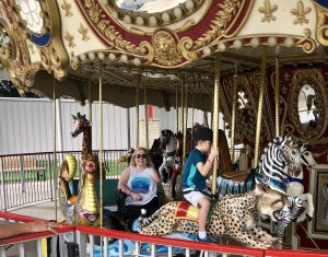 White woman in wheelchair with no legs and one arm on dragon platform on merry-go-round with nondisabled boy in front of her riding cheetah