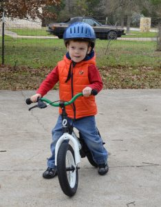 White toddler boy with blue helmet straddling green balance bike