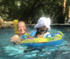 Color photograph of the author, a white blonde woman, in a pool with head and shoulders out of the water holding a child's colorful circular floaty toy with a toddler girl wearing a white hat inside the floaty. Both are smiling.