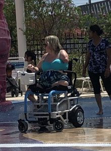 Color photograph of the author, A white woman with blond hair, a right arm, no legs, and a left arm amputated above the elbow, wearing a two piece bathing suit in the waterproof air powered wheelchair in a splash pad area.