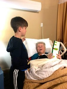 White boy with brown hair wearing track pants and a sweatshirt standing at the bedside of a elderly white woman who is looking at a card made by the boy, with green trees drawn on it.