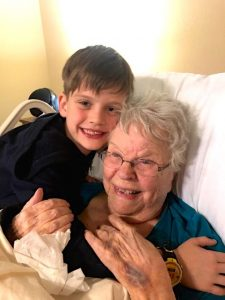 Color photograph of a white boy with medium brown hair hugging an elderly white woman with white hair in a hospital style bed, both smiling.