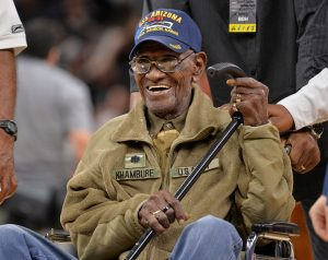 Color photograph of an elderly black man wearing a US S Arizona cap and military style jacket, sitting in a wheelchair and holding his cane wearing glasses. He is smiling.