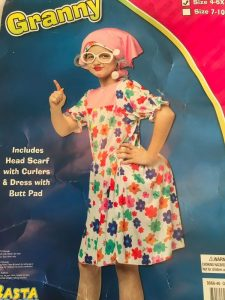 "Package costume for a child labeled ""granny"" reads ""includes head scarf with curlers and dress with but pad"". White girl pictured wearing head scarf, curlers, glasses, a flower print dress with padding on the seat area."