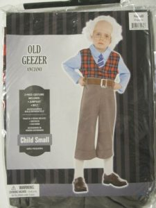"Package costume for child in size small labeled as ""old geezer"" features white school age child wearing a white wig, glasses, Miss matched clothing with pants pulled up nearly to his armpits and a significant gap between the bottom of the pants and his shoes revealing long white socks."